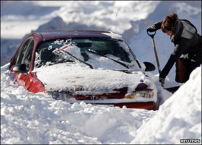 Woman digging out a car after heavy snow in Minneapolis in America.
