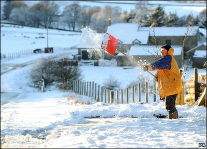 A woman clearing snow in County Durham in the north of England.