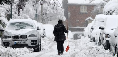 A woman carries a snow shovel as she walks along a snow-covered road near Farningham, Kent.