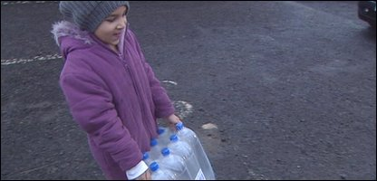 A child in Northern Ireland collects bottled water