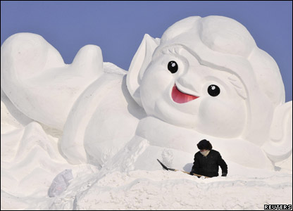 Sculpture and worker at the annual snow and ice festival in Harbin in China.