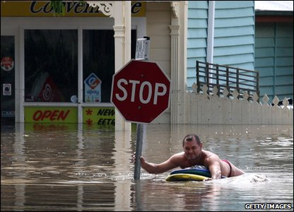 Flooding around the world - Australia - man in flooded part of Brisbane