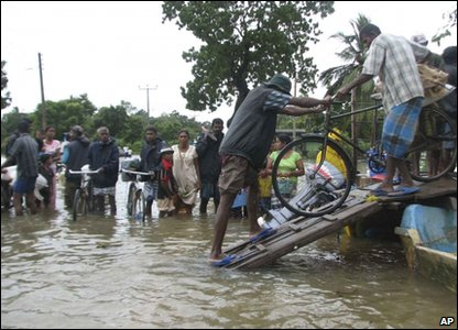 Flooding around the world - Sri Lanka - flood victims load their belongings onto a boat in Batticaloa