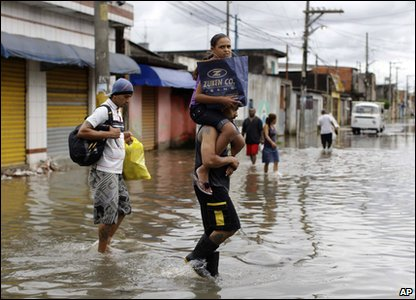 Flooding around the world - Brazil - people walk on a flooded street in Sao Paulo