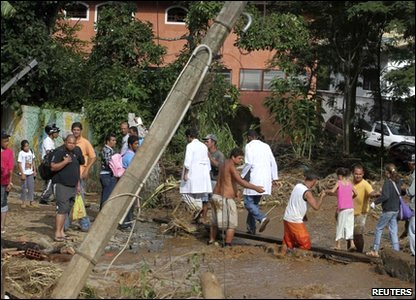 Flooding around the world - Brazil - people cross a street that's been hit by a landslide in Teresopolis