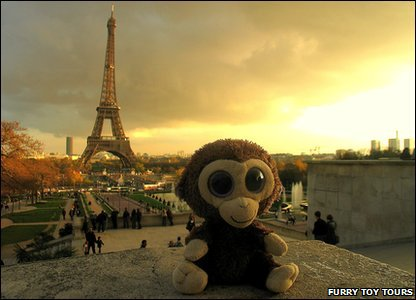Monkey toy in front of the Eiffel Tower