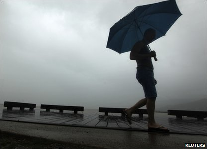 Someone walking along the waterfront in Cairns as the storm clouds gather