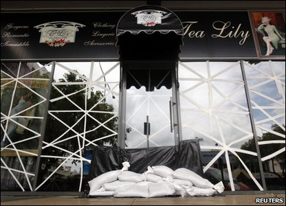 A cafe with taped windows and sandbags at the front door to try to protect it from waves that are expected to reach seven metres high