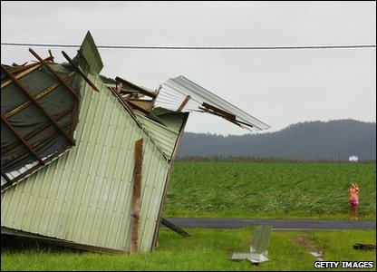 Cyclone Yasi aftermath in Queensland, Australia - person takes a photo of a damaged house in Innisfail