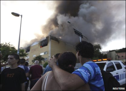 People watch the smoke from the fire.