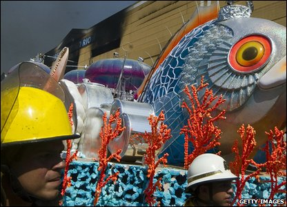 Firefighters walk next to a carnival float outside a burnt carnival warehouse .