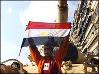 Protester in Egypt holding the national flag in front of a tank