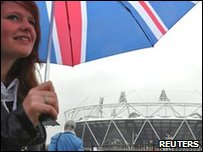 Woman with umbrella in front of London Olympic stadium