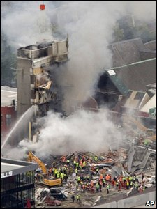 Rescue workers work to extinguish a fire at a collapsed building in central Christchurch, New Zealand