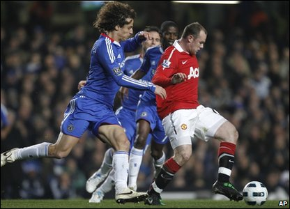 Chelsea player David Luiz, left, goes for the ball with Manchester United striker Wayne Rooney during their English Premier League match at Chelsea's Stamford Bridge