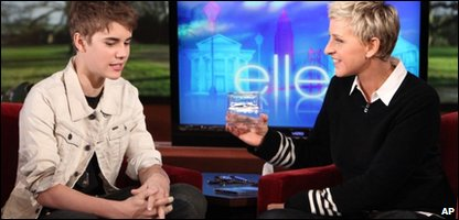 Justin Bieber chats to American talk show host Ellen DeGeneres, as she holds a box containing strands of his hair during an appearance on her show