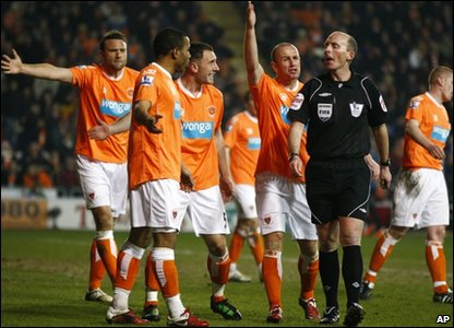 Blackpool players argue with the referee after he awarded a penalty to Chelsea