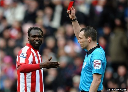 John Mensah is shown the red card by referee Kevin Friend.