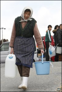 Old woman carries water in Ofunato