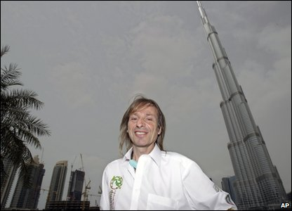 Alain Robert poses next to the world's tallest building