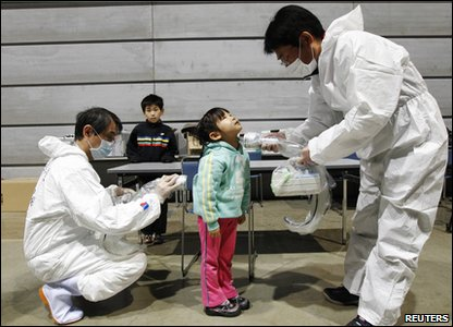 A five-year-old girl is tested for radiation at an evacuation centre in Japan