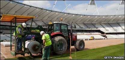 Construction workers lay the final pieces of turf at the Olympic Stadium