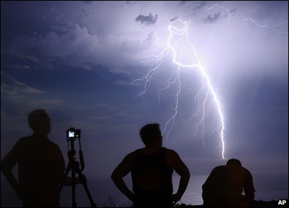 Three people watch a lightning bolt from a distance