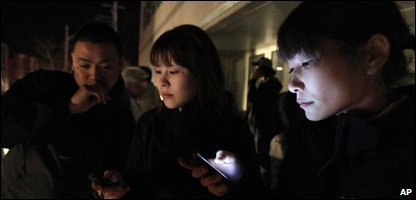Hotel guests check their mobiles for news after the earthquake
