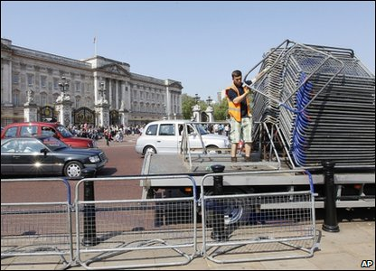 A worker helps set out row of barriers outside Buckingham Palace as final preparations are made in London for the royal wedding of Prince William and Kate Middleton.