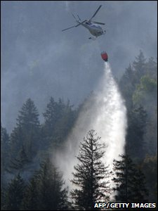 A helicopter dropping water onto a forest fire near the town of Viege in southern Switzerland