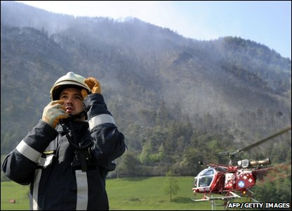 A fireman looks on behind a helicopter loading water to drop on a forest fire near the town of Viege in southern Switzerland