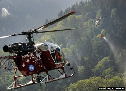 A helicopter on its way to drop water onto a forest fire near the town of Viege in southern Switzerland