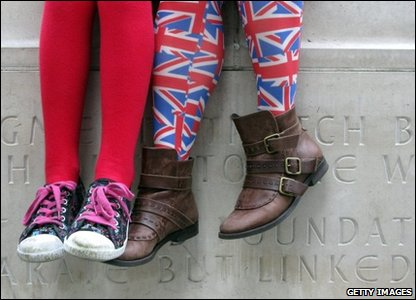 A woman wearing Union Jack tights sits outside Westminster Abbey