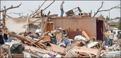 Residents clear debris at their house in the devastated town in Alabama