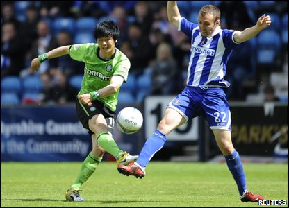 Celtic's Ki Sung-yeung (left) is challenged by Kilmarnock Liam Kelly during their Scottish Premier League soccer match at Rugby Park Stadium.