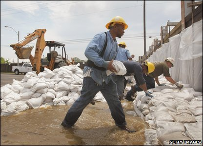 Workers lay down sand bags to try and prevent flooding