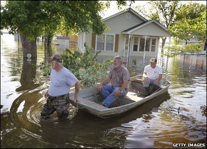 Local people travelling in a boat through their flooded neighbourhood in America