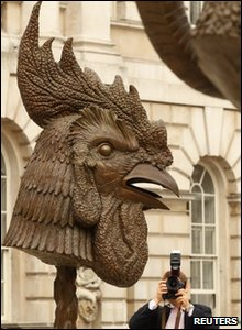 A man takes a photo of one of Ai WeiWei's bronze animal heads