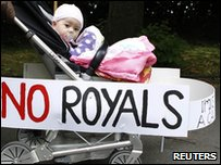 A baby in a pushchair with a 'no royals' sign attached