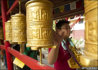 Here a devotee spins a prayer wheel at a Tibetan temple in Malaysia.