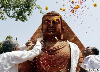 Devotees scatter flower petals on a Buddha statue on the occasion of Buddha Purnima festival, also know as Vesak Day, in the western Indian city of Ahmedabad