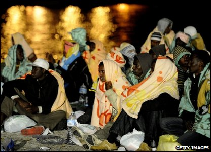 People wait at the port in Lampedusa after arriving from their home countries