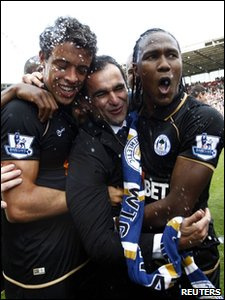 Wigan Athletic manager Roberto Martinez (C) is hugged by players Franco Di Santo (L) and Hugo Rodallega after his team beat Stoke 1-0 in the last game of the season and avoided relegation.