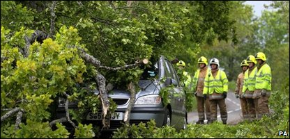 Emergency services tend to a car which has been trapped by a fallen tree near Dunblane, in Scotland