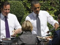 UK Prime Minister David Cameron (left) and American President Barack Obama dish out barbecue food