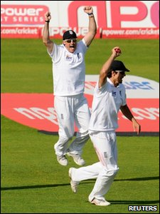 Cricketers Andrew Strauss and Alastair Cook  celebrate on the cricket pitch