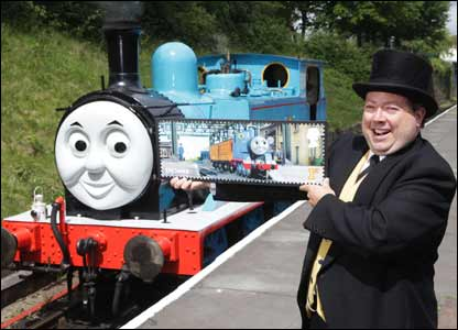 The Fat Controller - Sir Topham Hatt - shows off a large stamp as Thomas the Tank Engine looks on