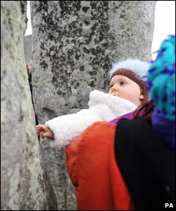 Baby touches a stone at Stonehenge, Wiltshire, on 21 June 2011