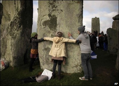 People hug the stones at Stonehenge, Wiltshire, on 21 June 2011