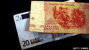 An old drachma note and a euro note